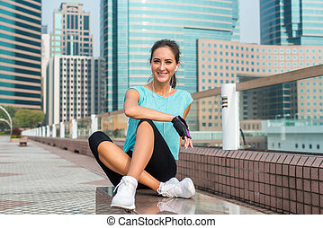 Fitness girl relaxing after workout session sitting on bench in city alley. Young athletic woman taking break from running, listening to music in earphones and smiling.