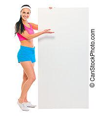 Fitness girl showing blank billboard