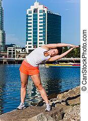 fitness girl side stretch - wide shot