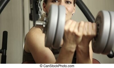 Fitness girl with dumbbells doing exercises in the gym