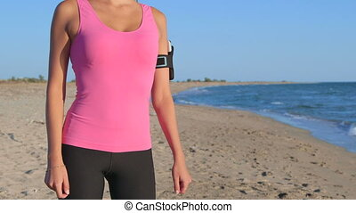 Fitness girl with phone in arm sport band exercising on the beach