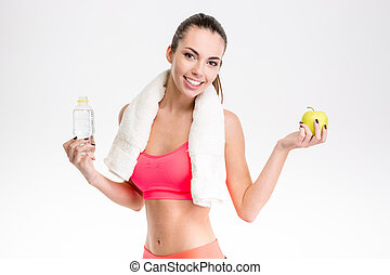 Fitness girl with towel holding bottle of water and apple -...
