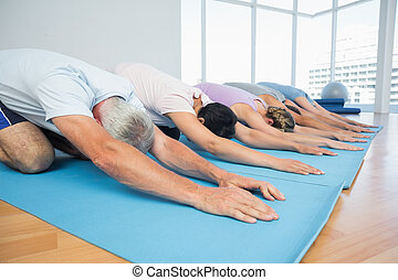 Fitness group in row at yoga class - Fitness group bowing in...