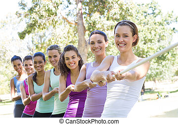 Fitness group playing tug of war on a sunny day