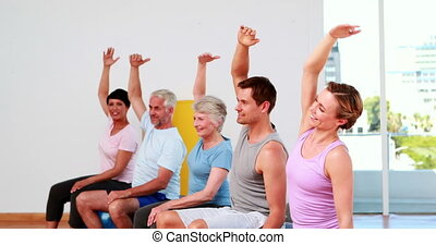 Fitness group sitting on exercise b