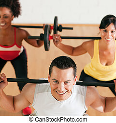 Fitness group with barbell in gym - Group of three people ...