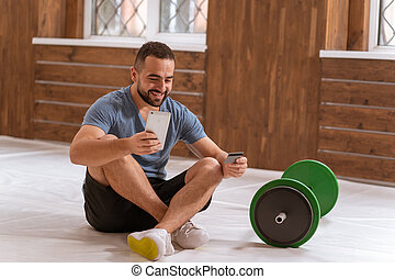 Fitness guy holds smartphone and debit or credit card buying online equipment or doing sport bets and gambling online. Modern digital sports life. Sport app on smartphone