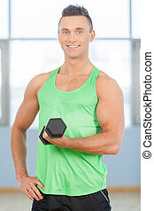Fitness guy. Young handsome man in green shirt is lifting weights