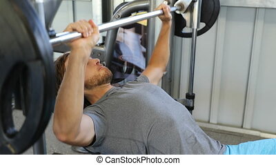 Fitness gym man training chest muscles doing flat bench press with barbell