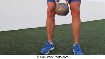 Fitness gym training man lifting heavy kettlebell weight for legs workout.