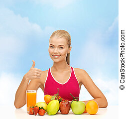 smiling woman with organic food or fruits on table