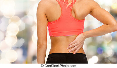 close up of sporty woman touching her back