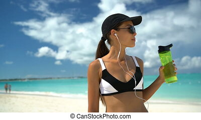 Fitness healthy sporty Asian runner woman running on beach drinking water bottle