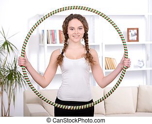 Portrait of young beautiful woman doing fitness with a hoop at home