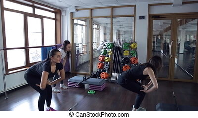 Fitness instructor demonstrates exercises to clients next to mirror