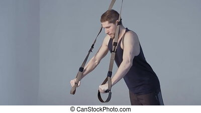 Fitness instructor exercising suspension training trx on light purple background. Fitnes video tutorial. Fitness concept. Sports concept. Prores 422.