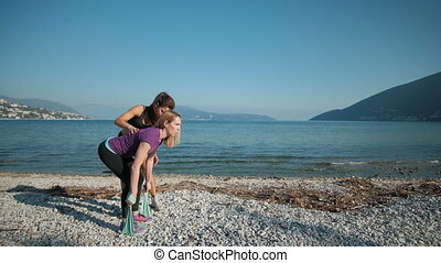 Fitness instructor help doing exercises to clients outdoors near lake