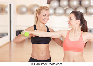 Fitness instructor helping woman in gym