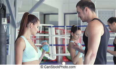 Fitness instructor shows a young girl athlete how to do exercises with dumbbells