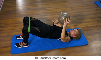 Fitness instructor working out on mat with ball in hands and rope on legs during pilates session