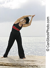 Fitness is fun - woman stretches by the ocean