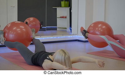 Fitness ladies doing abdominal crunches with ball in sports club.
