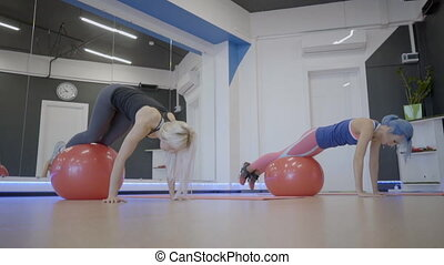 Fitness ladies doing exercise with balls in sports club.