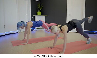 Fitness ladies doing plank exercise in motion in sports club.