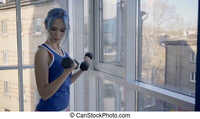 Fitness lady doing biceps dumbbell curls in gym room. Woman...
