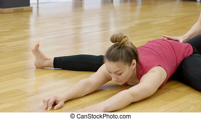 Fitness lady is stretching body with trainer in sports club....
