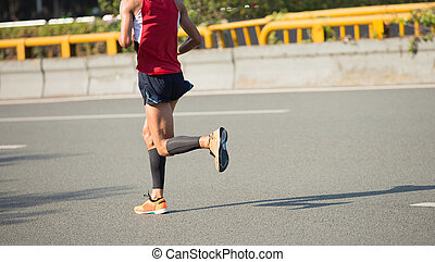 fitness male marathon runner running on city road