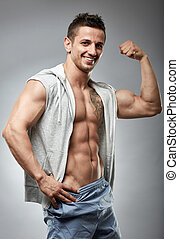 Fitness male model posing on gray background