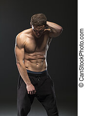 fitness male model with six pack on black