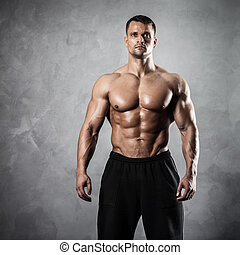 Fitness male model - Handsome athletic man posing on gray...
