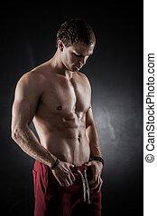 Fitness male model - Handsome athletic man posing on dark...