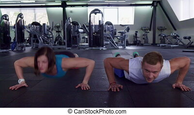 Fitness man and woman do push ups at the gym