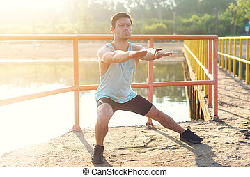 Fitness man athlete warming up legs before jogging outdoors