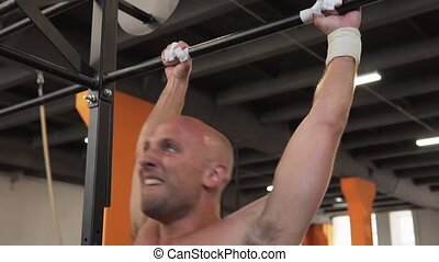 Fitness man doing bar muscle-up workout in gym