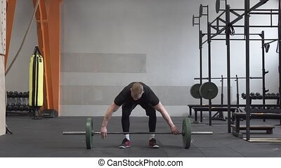 Fitness man doing barbell snatch exercise in gym