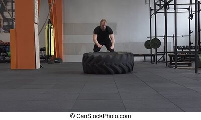 Fitness man doing big tire flips exercise in gym