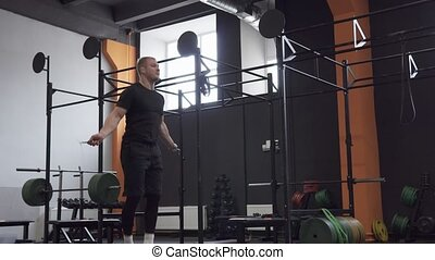 Fitness man doing double jumps rope exercise in gym