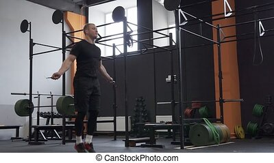 Fitness man doing double jumps rope exercise in gym, panning shot