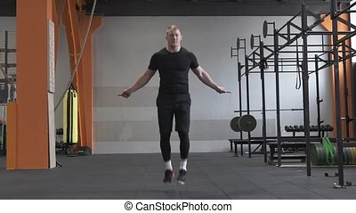 Fitness man doing double jumps rope in the gym