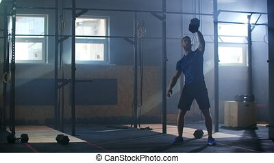 Fitness man doing dumbbell snatch exercise during functional training at gym. Slow motion.