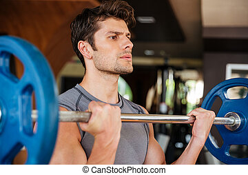 Fitness man doing exercises with barbell in gym