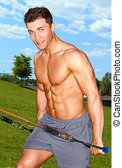 Fitness man doing expand exercises in park at summer