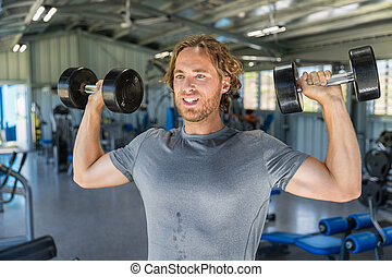 Fitness man doing military presses or standing dumbbell press exercise training in gym with free weights