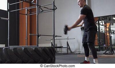 Fitness man doing sledgehammer swing exercise in gym