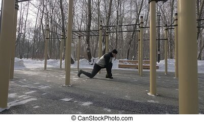 Fitness man doing squat exercise on winter sports ground...