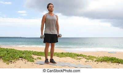 Fitness man exercising biceps with dumbbells in Bicep Curl arm exercise on beach. Fit male sport fitness model showing correct technique in classic weight lifting workout exercise. REAL TIME.